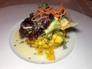 Mango-Salat angerichtet mit Möhrenstreifen auf weißem Teller