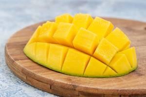 Mangofrucht als Igel angerichtet, liegt auf einer weiß-blauen Küchenzeile