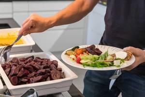 Mann am Büfettstand hält einen gesunden Essensteller mit Salat, Früchten und geschnittener rote Bete