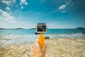 Mann am Strand mit Unterwasserkamera in der Hand