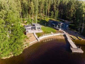 Mann auf einem Holzsteg schießt ein Drohnenfoto von der Villa Jolla an Finnlands längstem See Päijänne, mit nordischem Wald im Hintergrund