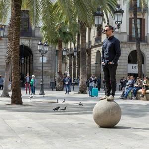 Mann balanciert auf steinerner Kugel vor den behelmten Laternen von Antoni Gaudí am historischen Placa Reial in Barcelona, Spanien