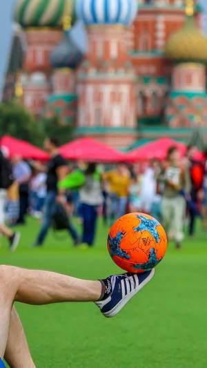 Mann balanciert Fußball auf dem Fuß