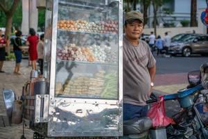 Mann bietet frittierte Snacks aus Verkaufsstand auf Motorroller an, Flower Street, Ho Chi Minh City, Vietnam