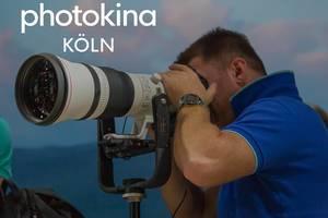 """Mann blickt durch ein professionelles und gigantisches Objektiv auf einem Manfrotto-Stativ, neben dem Bildtitel """"Photokina Köln"""""""