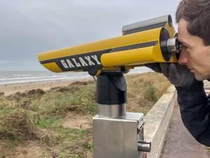 Mann blickt durch fest installiertes Fernrohr am Strand in Zandvoort, Niederlande