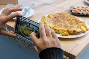 Mann fotografiert das Büfett mit seinem Smartphone