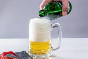 Mann gießt helles Bier in Glas und macht Schaumkrone vor weißem Hintergrund
