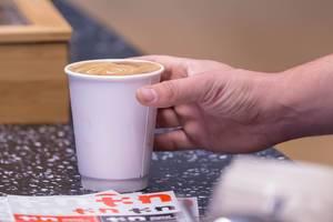 Mann greift nach Cappuccino in Pappbecher