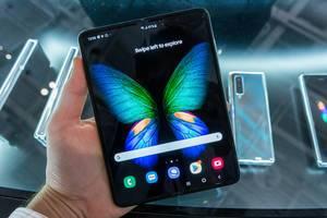 Mann hält das faltbare Handy Galaxy 5G von Samsung mit großem, faltbaren Infinity Flex Display in der Hand