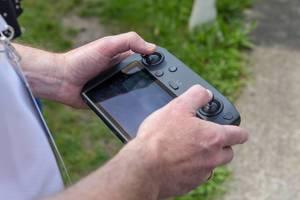Mann hält den DJI Mavic 2 Smart Controller mit 5,5 Zoll Bildschirm und automatischer Verbindung zur Drohne