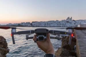 Mann hält die Drohne DJI Mavic 2 in der Hand, um sie über das Mittelmeer und die Insel Paros, Griechenland, fliegen zu lassen