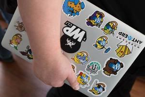 Mann hält ein Notebook in der Hand mit vielen Stickern auf dem Rückdeckel