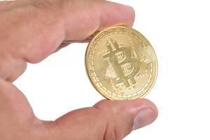 Mann hält eine goldene Bitcoinmünze in der Hand, vor weißem Hintergrund