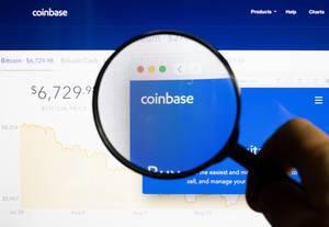 Mann hält eine Lupe über dem Coinbase-Logo