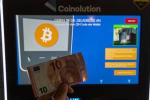 Mann hält einen 10 Euro Schein vor einen Coinolution Bitcoin Geldautomat, um ihn gegen die Kryptowährung einzutauschen