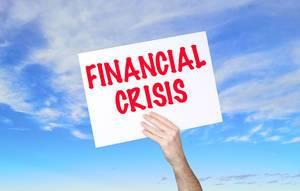 """Mann hält Schild mit """"Financial crisis / Finanzielle Krise"""" Text und blauem Himmel als Hintergrund"""