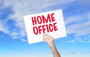 """Mann hält Schild mit """"Home Office"""" Text und blauem Himmel als Hintergrund"""