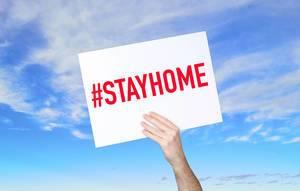 """Mann hält Schild mit """"#stayhome"""" Text und blauem Himmel als Hintergrund"""