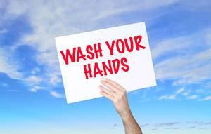 """Mann hält Schild mit """"Wash your hands / Wasch dir die Hände"""" Text und blauem Himmel als Hintergrund"""