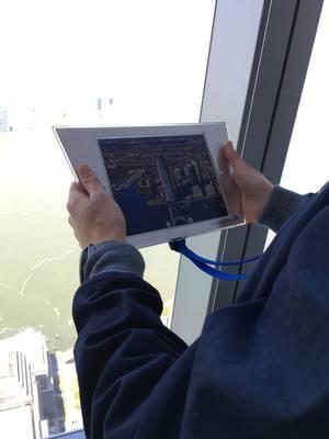 Mann hält Tablet mit einem Foto des Gebäudes Colgate Center in den Händen in Jersey City, USA
