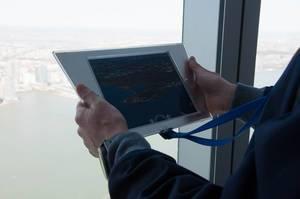 Mann hält Tablet mit einem Foto von Jersey City in den Händen, USA