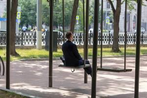 Mann im Anzug auf einer großen Schaukel im Park