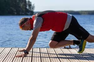 Mann in Asics-Sportlerhoser macht Fitnessübungen auf einer Holzterrasse am Päijänne-See am gleichnamigen Nationalpark in Finnland