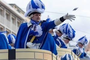 Mann in blau-weißer Uniform wirft Zuschauern Päckchen zu - Kölner Karneval 2018