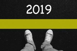 Mann in Converse Turnschuhen steht vor Jahreszahl 2019 auf schwarzem Asphalt