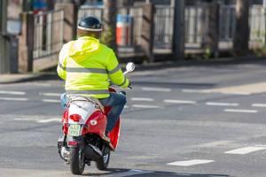Mann in gelber Jacke fährt Motorroller auf einer leeren Straße