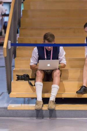 Mann in Lederhosen bedient Macbook auf einer Treppe, Absperrung als Zensur