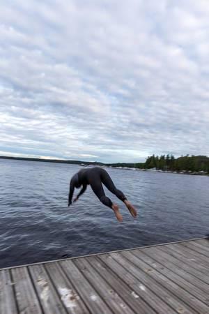 Mann in Taucheranzug macht einen Kopfsprung in den See Päijänne nahe Lahti in Finnland