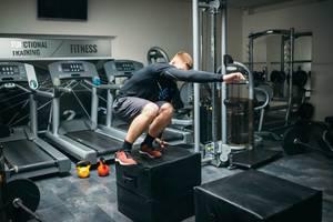 Mann macht Boxsprung in Fitnessstudio mit Laufbändern und Fitnessgeräten im Hintergrund