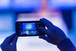 Mann macht ein Foto mit Smartphone bei der Rede von Tarana Burke auf dem Bits & Pretzels Festival in München