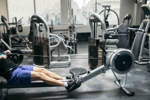 Mann macht Fitnessübung auf Rudergerät in Fitnessstudio