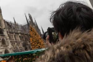 Mann macht Foto von Kölner Dom mit Weihnachtsbaum und Weihnachtsmarkt auf Domplatte