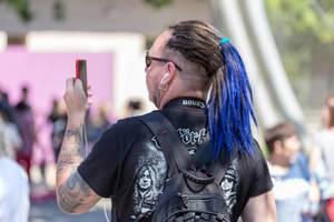 Mann mit Dreadlocks fotografiert mit seinem Handy