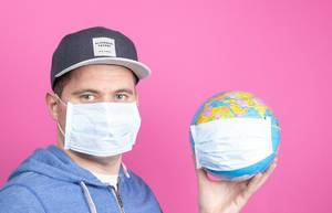 Mann mit Gesichtsmaske hält eine Weltkugel mit Gesichtsmaske auf pinkem Hintergrund