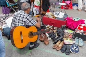 Mann mit Gitarre schaut sich gebrauchte Schuhe am Naschmarkt Flohmarkt an