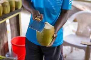 Mann mit Hackbeil beim Aufschneiden einer grünen Kokosnuss in einer Strandbar am Anse Source d