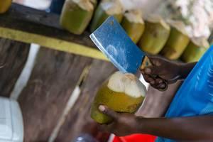 Mann mit Hackbeil schneidet eine grüne Kokosnuss an einer Strandbar am Anse Source d