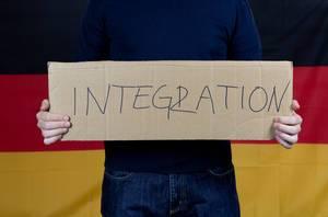 Mann mit Integration-Transparent vor deutscher Flagge