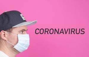 Mann mit Kappe trägt Gesichtsmaske und schaut auf das Wort Coronavirus auf pinkem Hintergrund