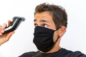 Mann mit Mundschutz schneidet sich die Haare selber: die Friseure haben in Corona-Zeiten zu