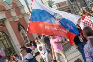 Mann mit russischer Flagge filmt mit seinem Handy