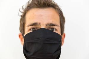 Mann mit schwarzem Mehrweg-Mundschutz, der nur die Augen sichtbar lässt: Nahaufnahme Porträt vor weißem Hintergrund