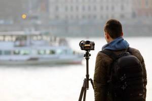 Mann mt Stativ fotografiert ein Schiff auf der Donau in Budapest, Ungarn