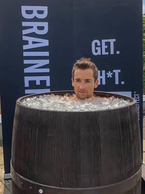 Mann nimmt ein Eisbad in einem alten Holzfass, um sich nach dem harten Training und Sport zu regenerieren
