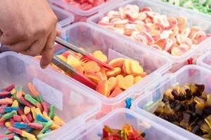 Mann nimmt mit Zange Gummi Süssigkeiten aus Plastikgeschirren an einem Markt